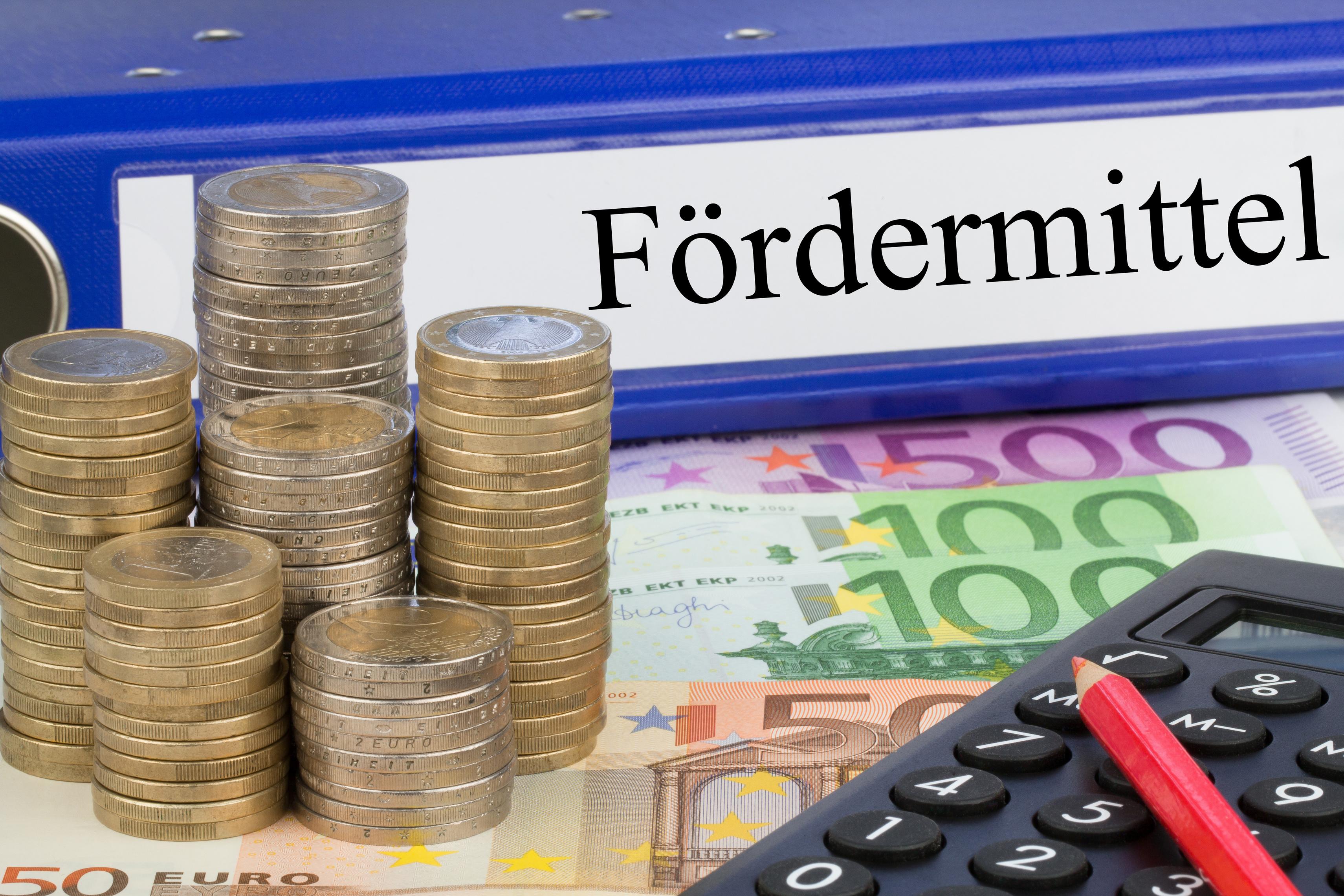 Abbildung zeigt symbolisch Geld und Taschenrechner für Fördermittel