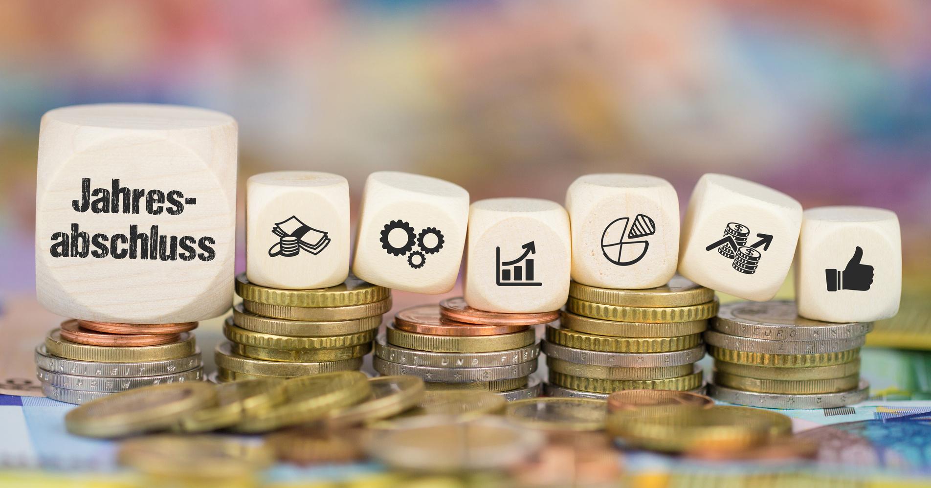 Abbildung zeigt Euro-Geldstücke und Würfel mit Symbolen für Jahresabschluss