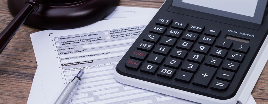 Abbildung zeigt ein Steuererklärungs-Formular und einen Taschenrechner