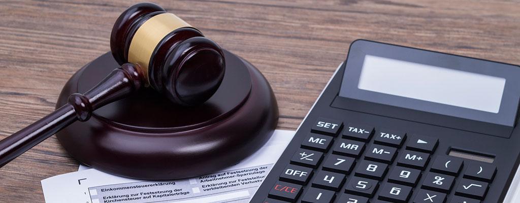 Abbildung zeigt einen Richterhammer, ein Steuererklärungs-Formular und einen Taschrechner