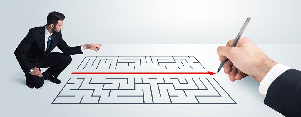 Abbildung zeigt Personen, die einen Weg durch ein Labyrinth suchen