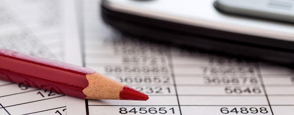 Abbildung zeigt Zahlentabellen und einen roten Stift
